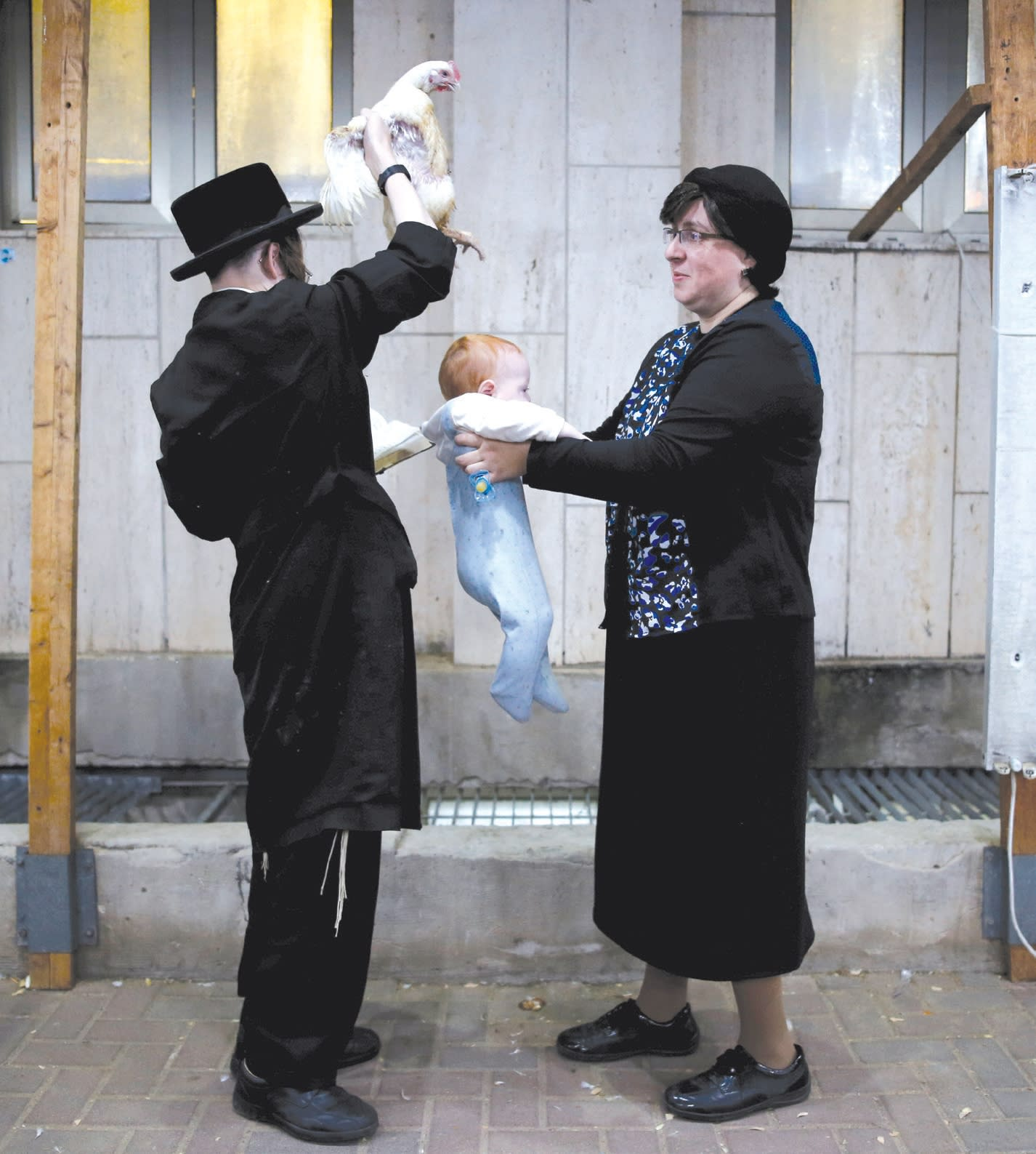 "A haredi man holds a chicken over a baby as he performs the ""kapparot"" ritual. (credit: REUTERS / Amir Cohen)"