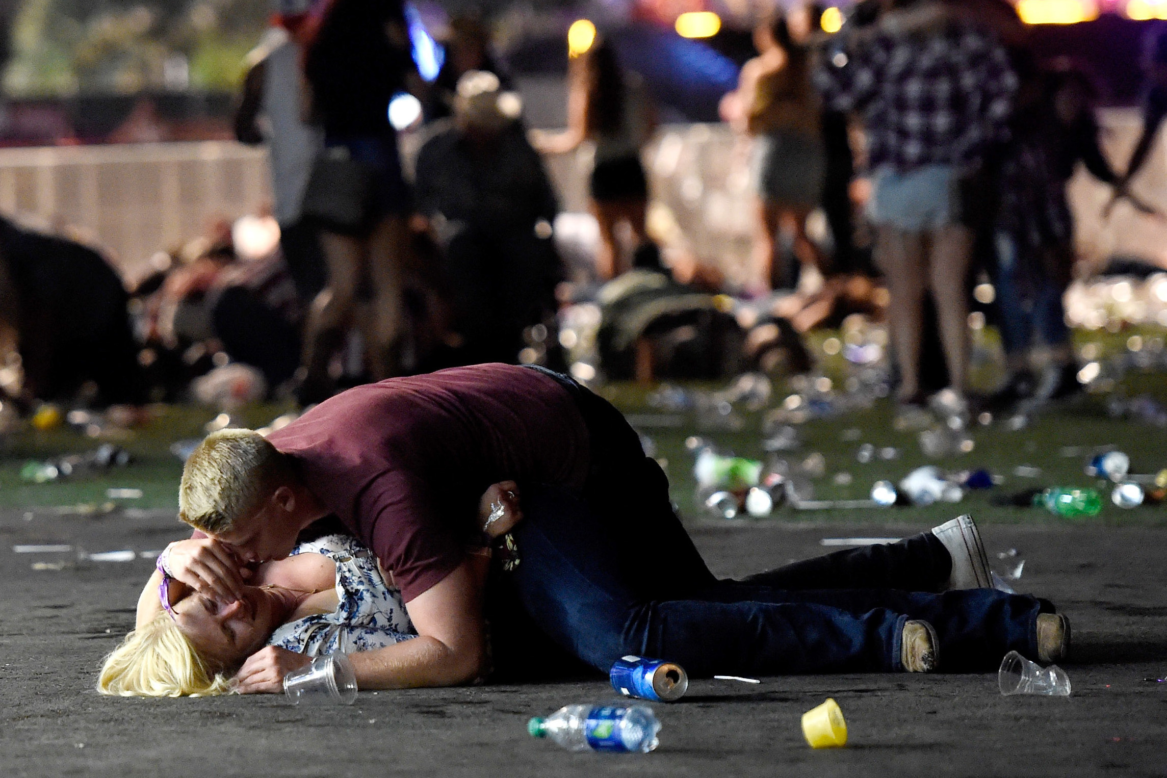 A man lays on top of a woman as people flee a mass shooting in Las Vegas, Nevada (DAVID BECKER / GETTY IMAGES / AFP)