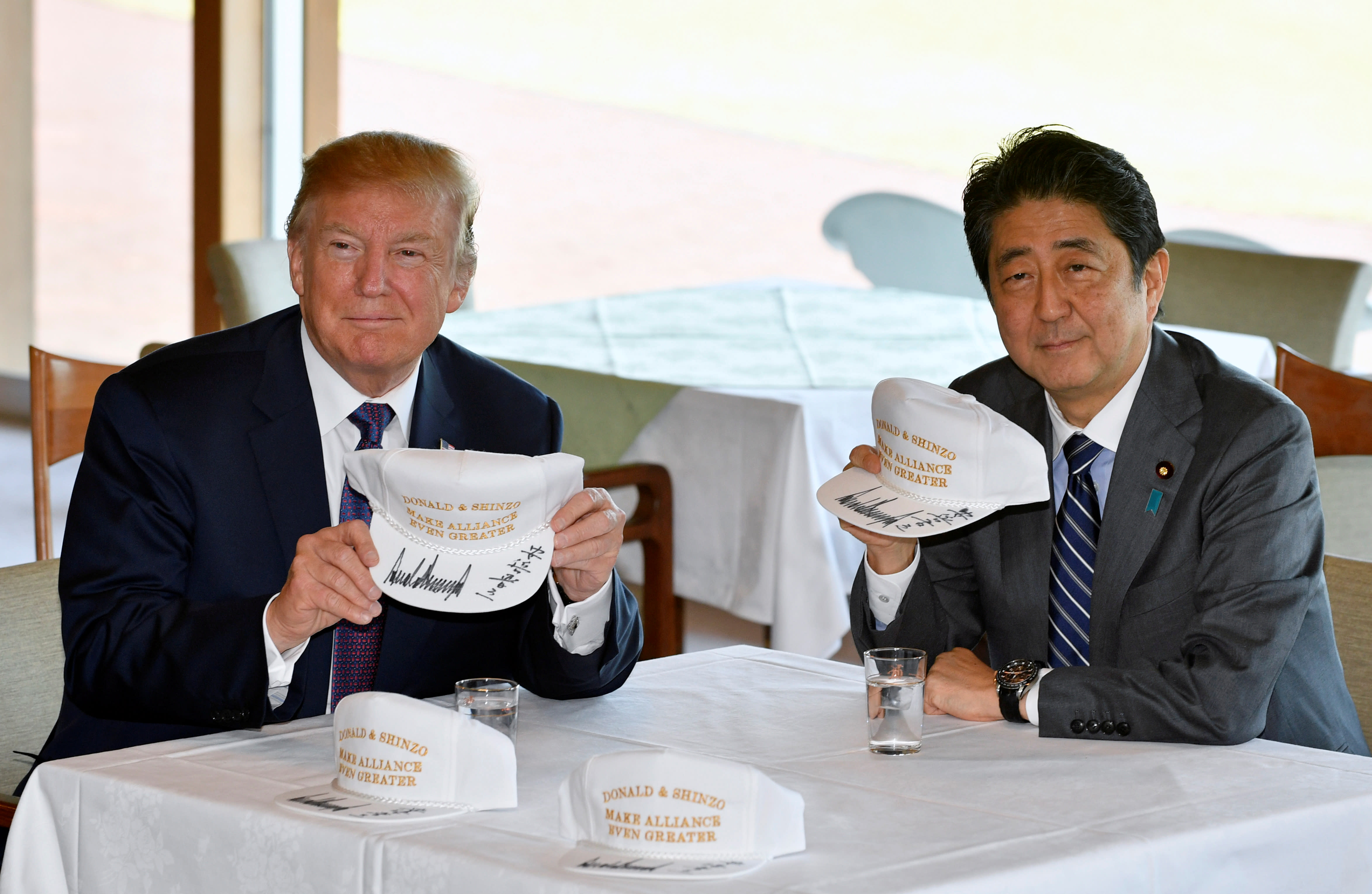 US President Donald Trump and Japanese Prime Minister Shinzo Abe pose after they signed hats. (REUTERS / FRANK ROBICHON / POOL)