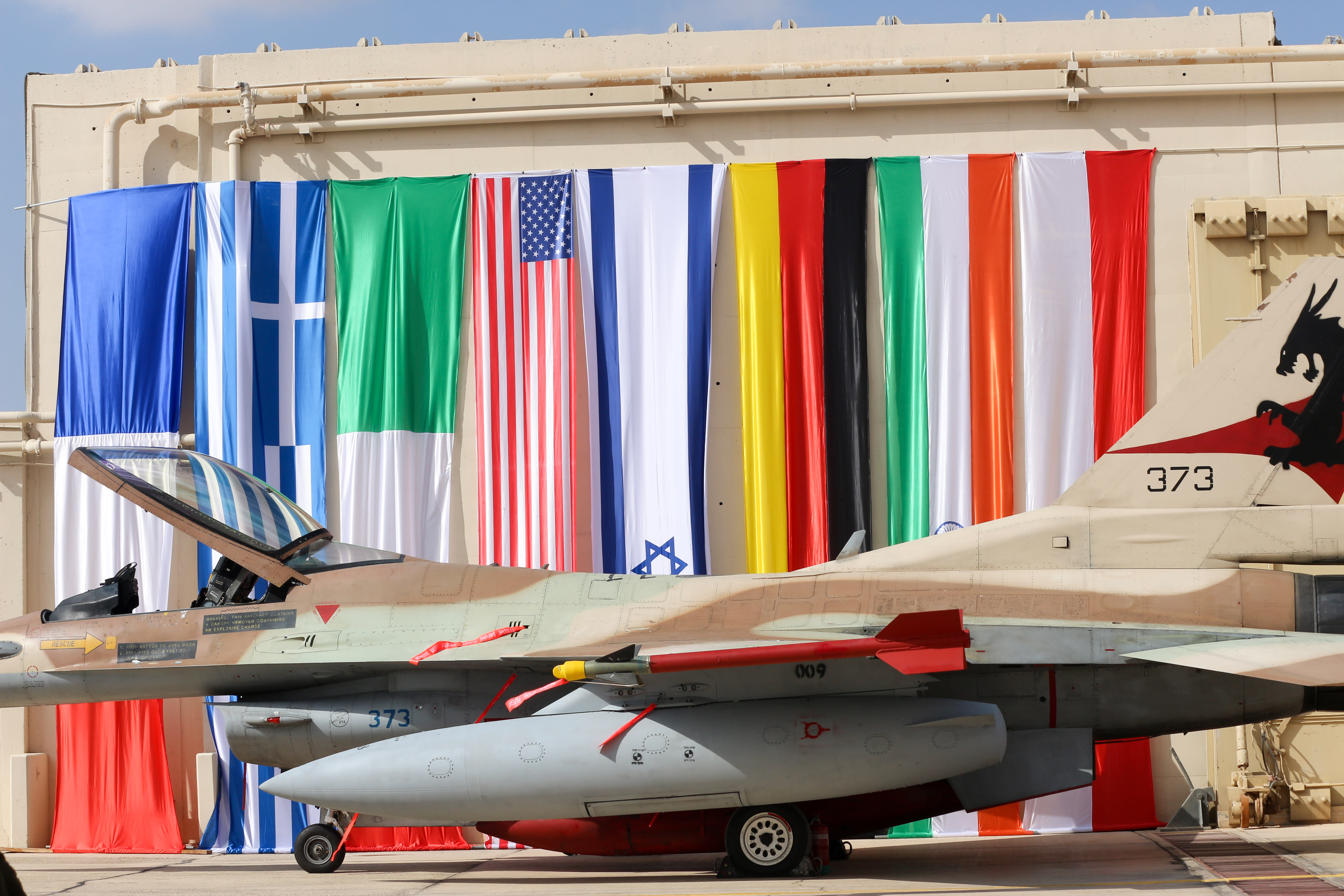 An Israeli F16 stationed next to flags of participating nations (ANNA AHRONHEIM)