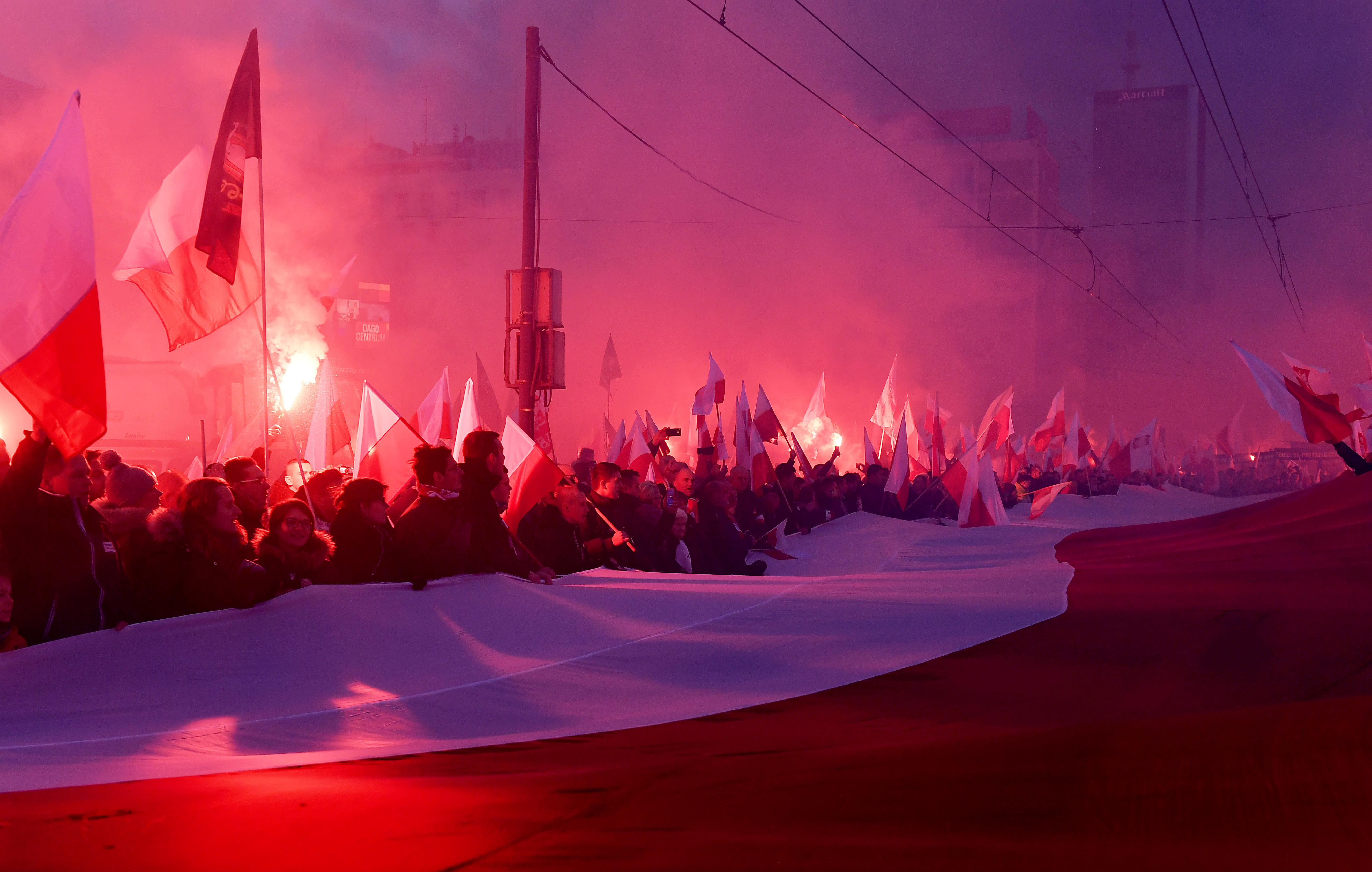 Demonstrators burn flares and wave Polish flags during Poland's Independence Day in Warsaw (AFP/JANEK SKARYNSKI)