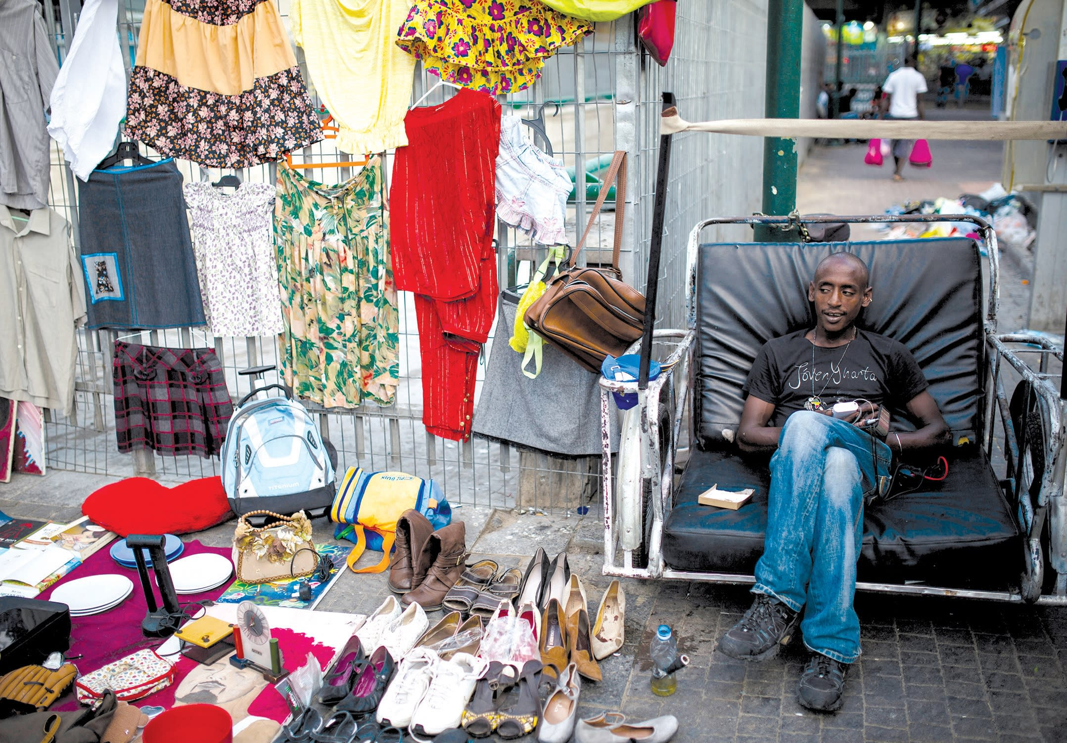 AN AFRICAN MIGRANT street vendor waits for customers in South Tel Aviv in July. (REUTERS/AMIR COHEN)