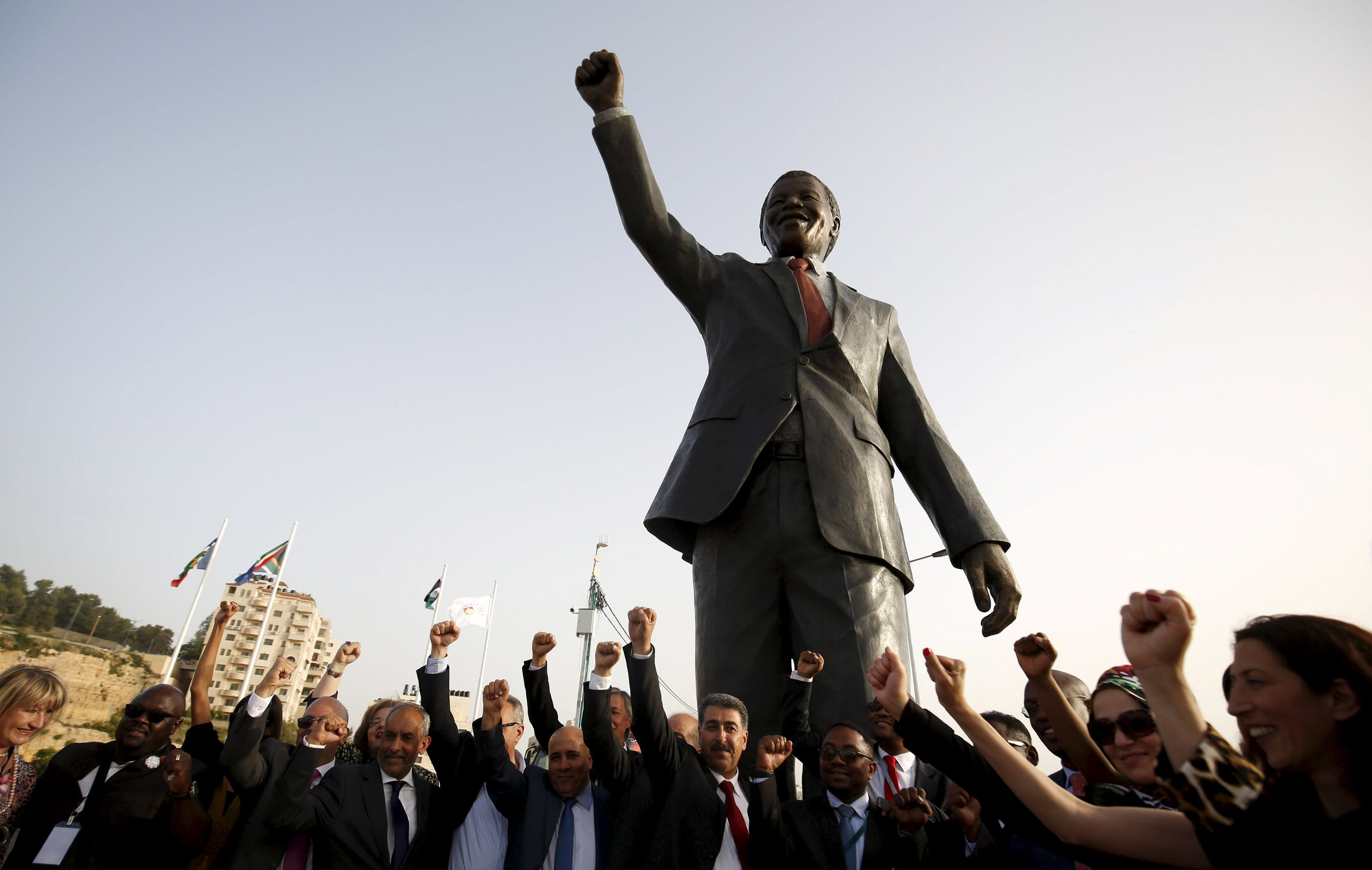 People cheer in front of a Mandela statue during the inauguration of Nelson Mandela Square in the West Bank city of Ramallah. (Mohammad Torokman / Reuters)
