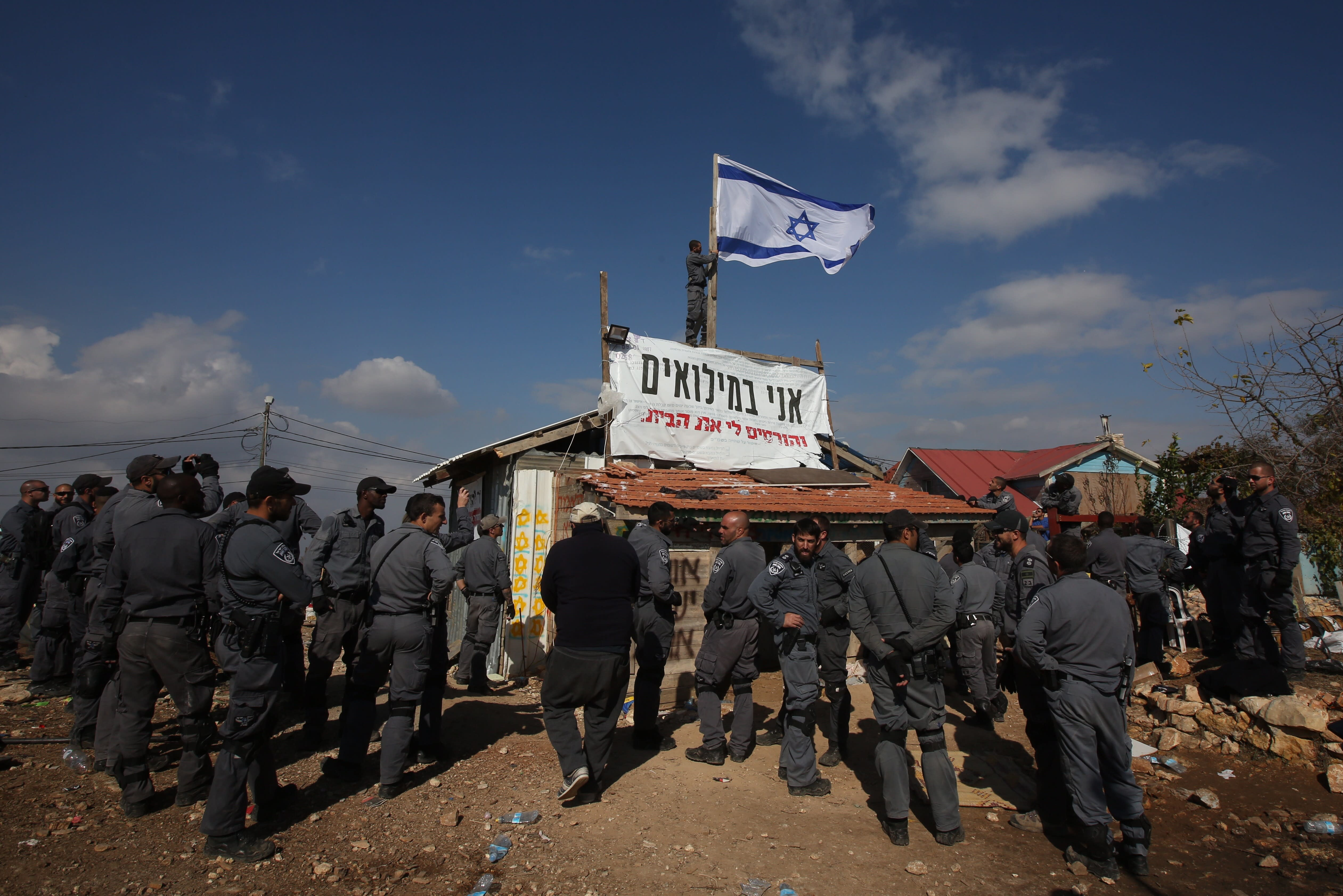 Border police remove an Israeli flag from a condemned building in Netiv Ha'avot