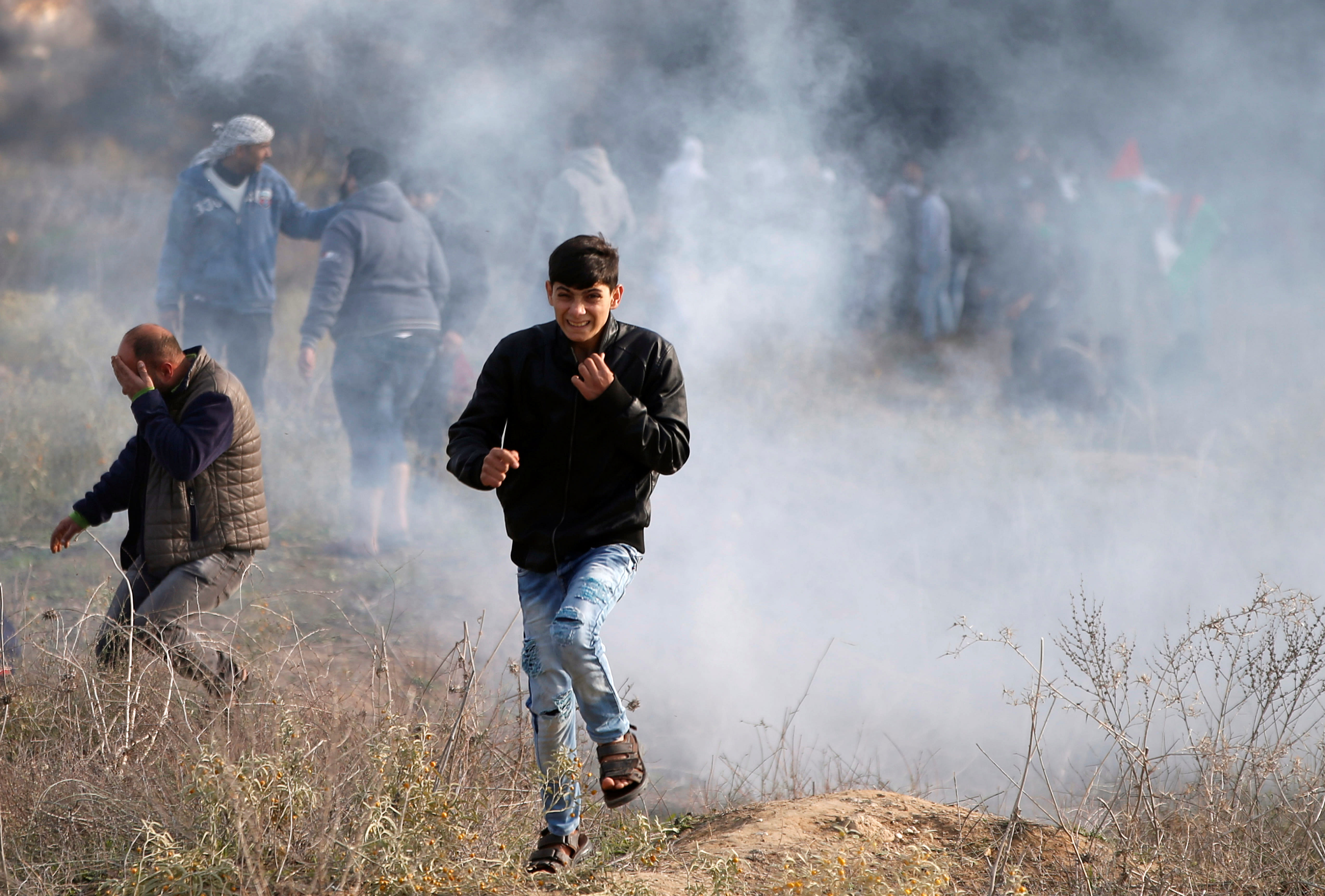 """Palestinian protesters react to tear gas fired by Israeli troops during clashes as Palestinians call for a """"day of rage"""" in response to U.S. President Donald Trump's recognition of Jerusalem as Israel's capital, near the Jewish settlement of Beit El, near the West Bank city of Ramallah December 8, 2017"""