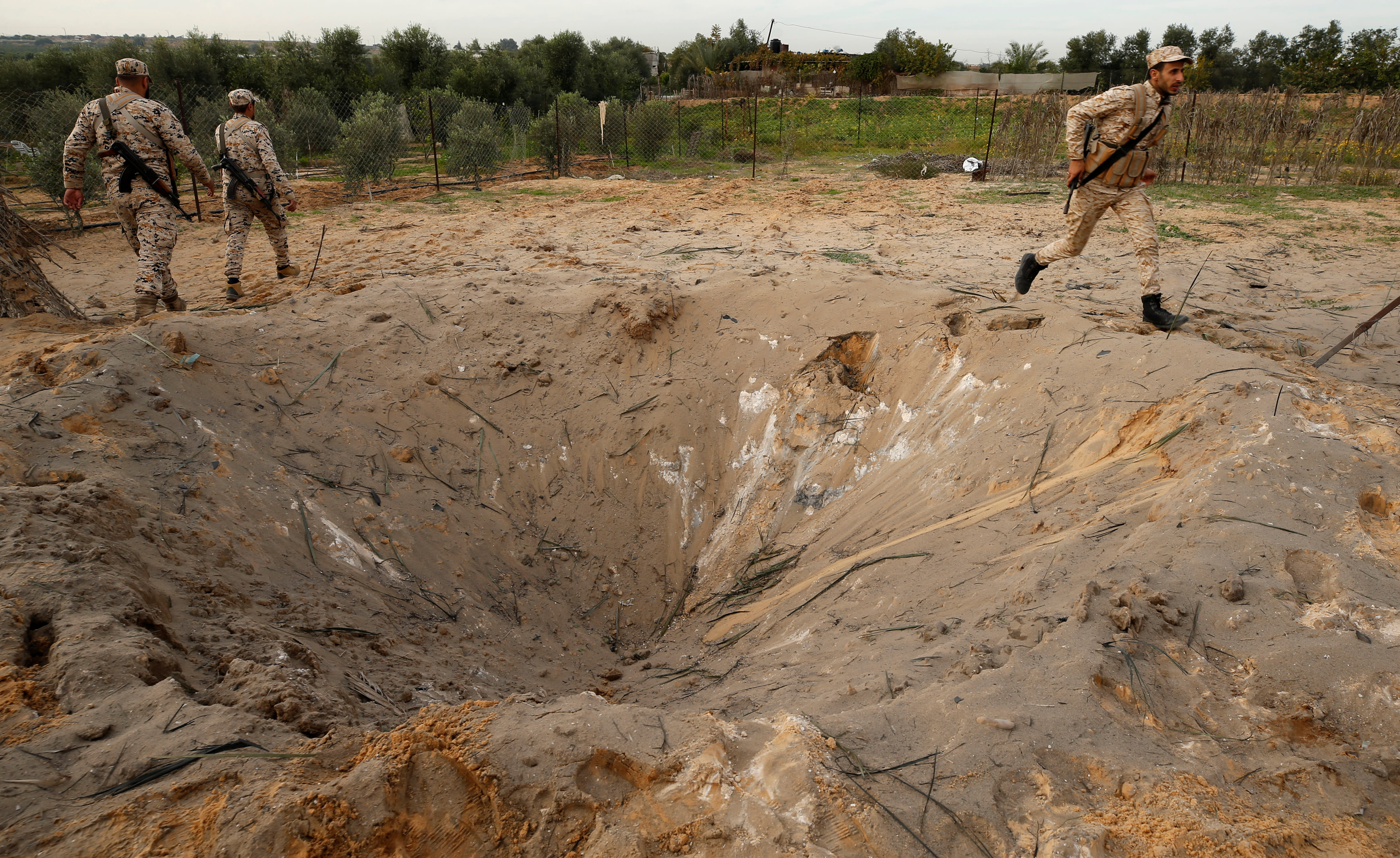Members of Palestinian Hamas security forces survey the scene of an explosion in the northern Gaza Strip