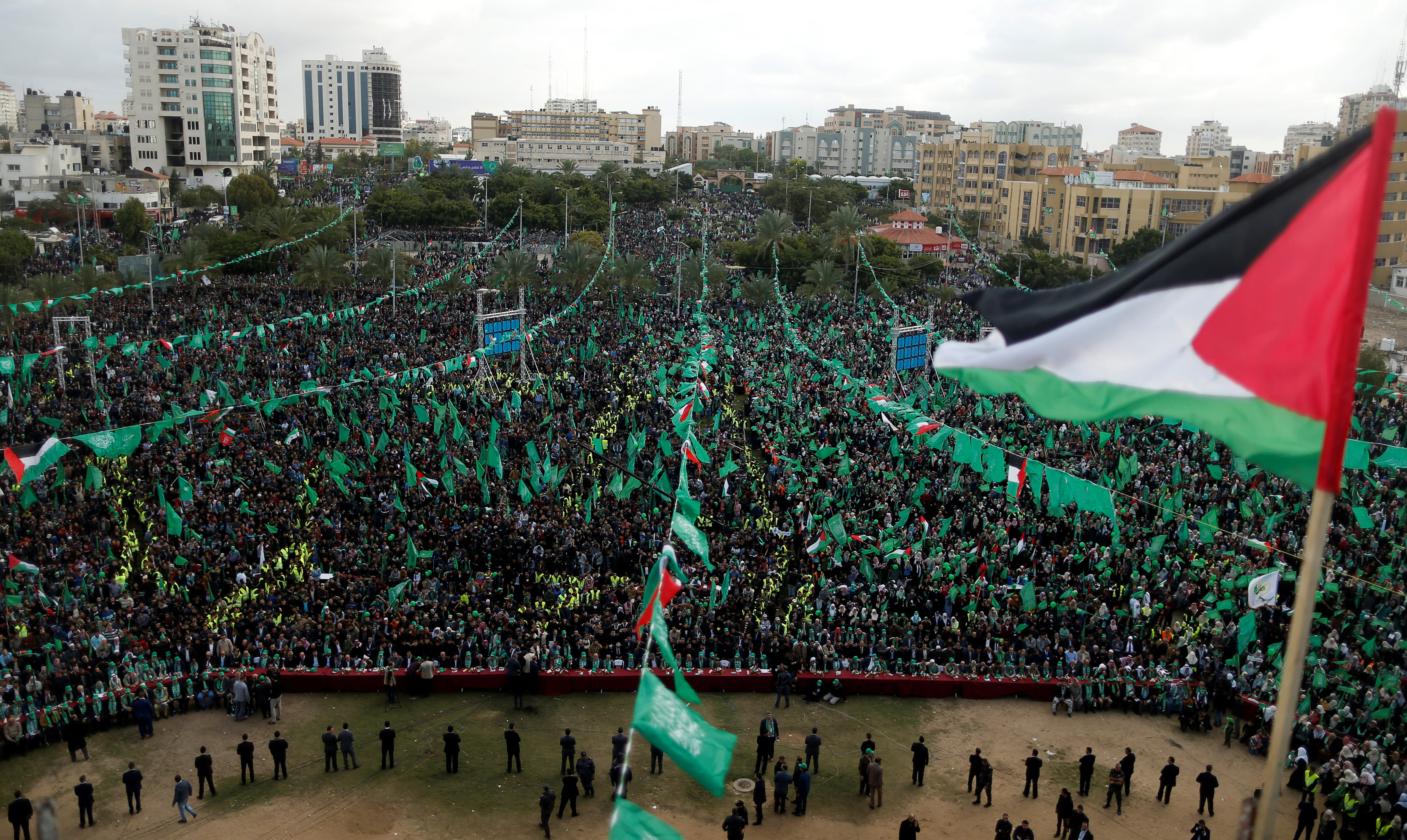 A Palestinian flag flies as Hamas supporters take part in a rally marking the 30th anniversary of Hamas' founding in Gaza City, December 14, 2017 (SUHAIB SALEM / REUTERS)