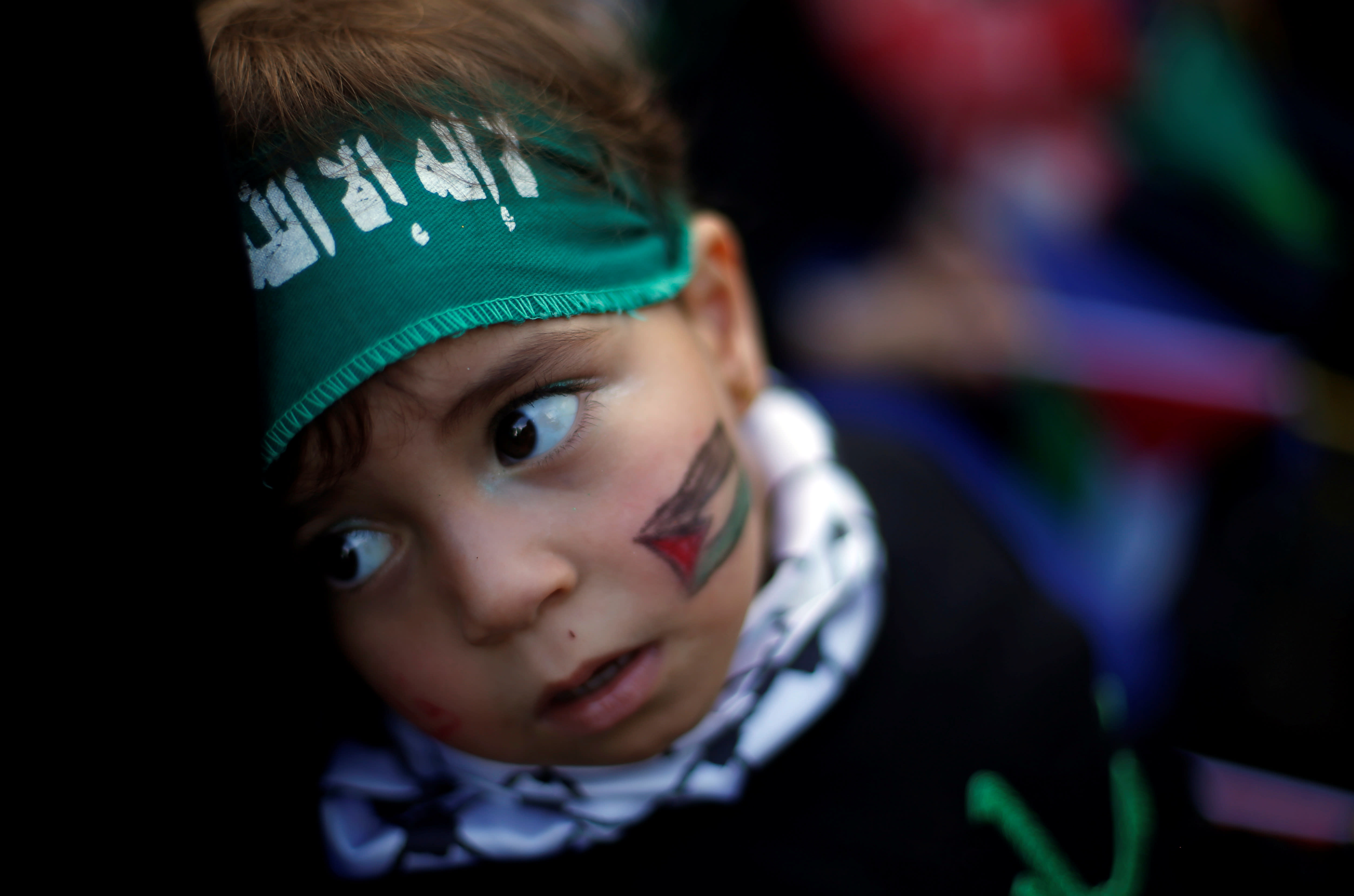 A Palestinian child wearing a Hamas headband takes part in a rally marking the 30th anniversary of Hamas' founding in Gaza City December 14, 2017 (SUHAIB SALEM/REUTERS)