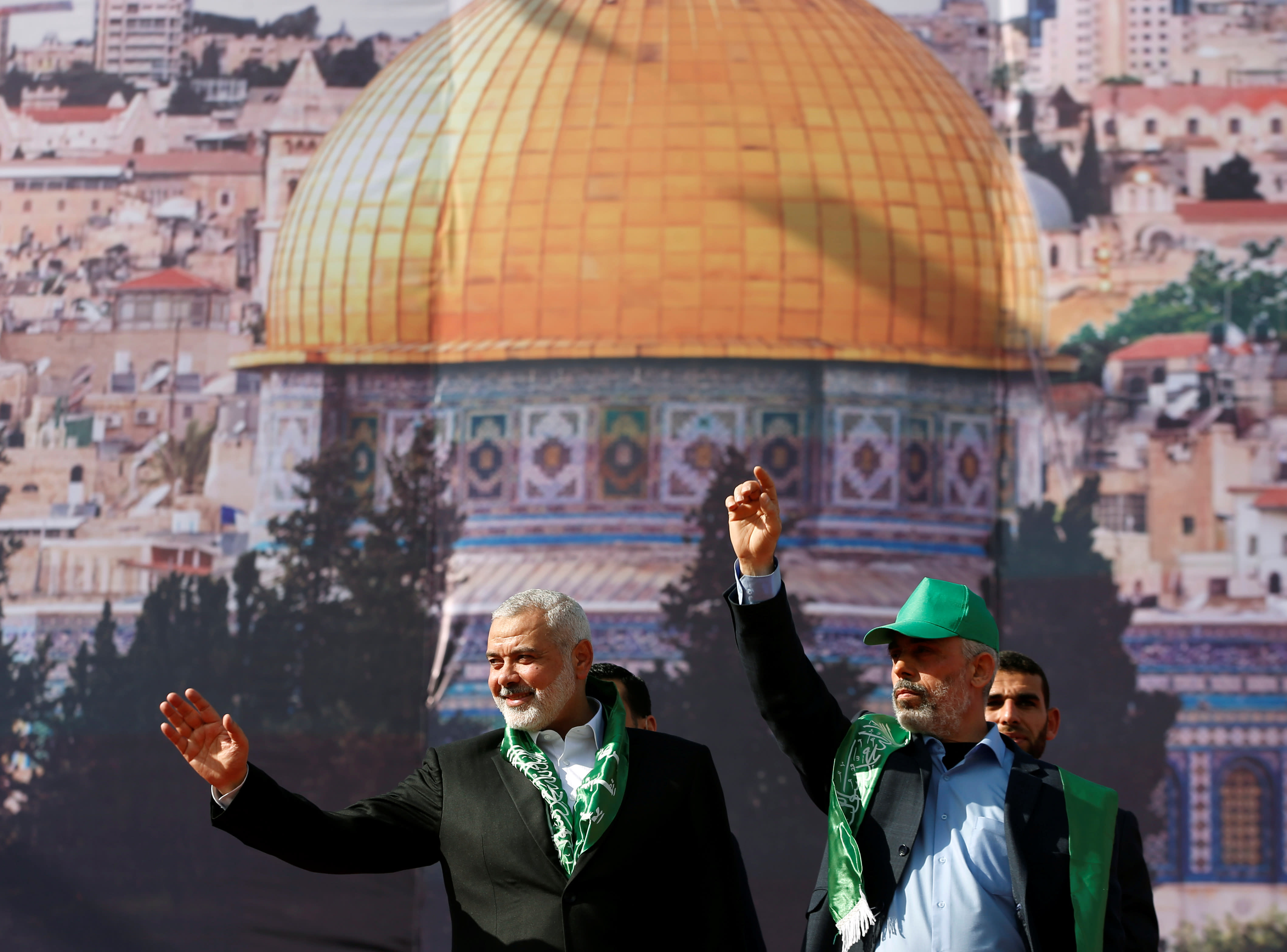 Hamas Chief Ismail Haniyeh and Gaza's Hamas Chief Yehya Al-Sinwar gesture to supporters during a rally marking the 30th anniversary of Hamas' founding in Gaza City, December 14 2017 (MOHAMMED SALEM/REUTERS)