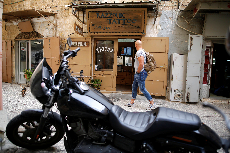 A man walks past the studio of tattoo artist Wassim Razzouk in Jerusalem's Old City (AMIR COHEN/REUTERS)