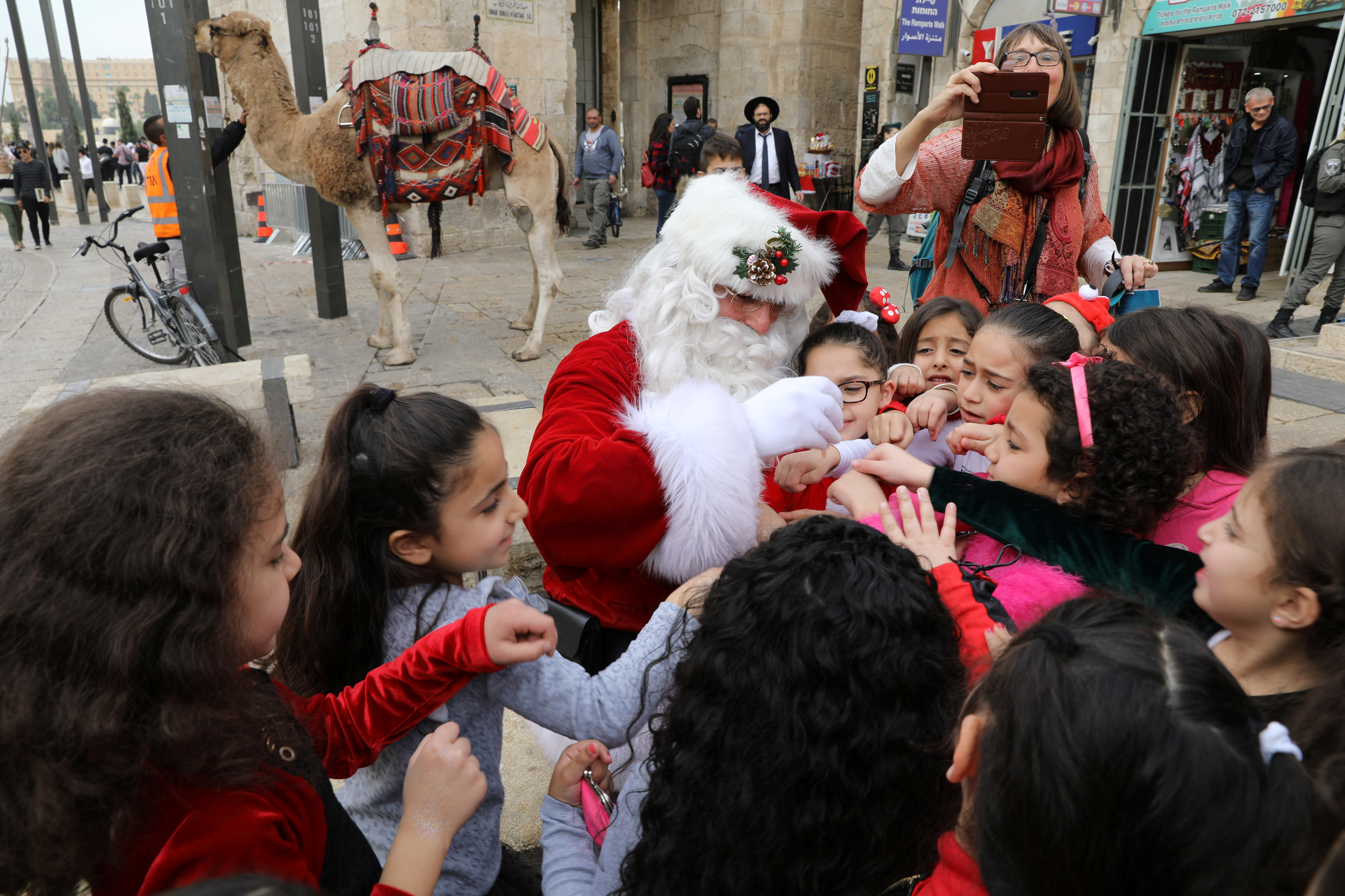 A group of girls stand around Israeli-Arab Issa Kassissieh, wearing a Santa Claus costume, during the annual Christmas tree distribution by the Jerusalem municipality in Jerusalem's Old City December 21, 2017