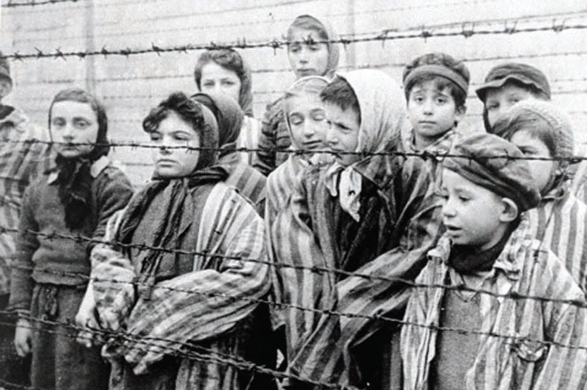 Child survivors of Auschwitz stand behind a barbed wire fence. (Wikimedia Commons)