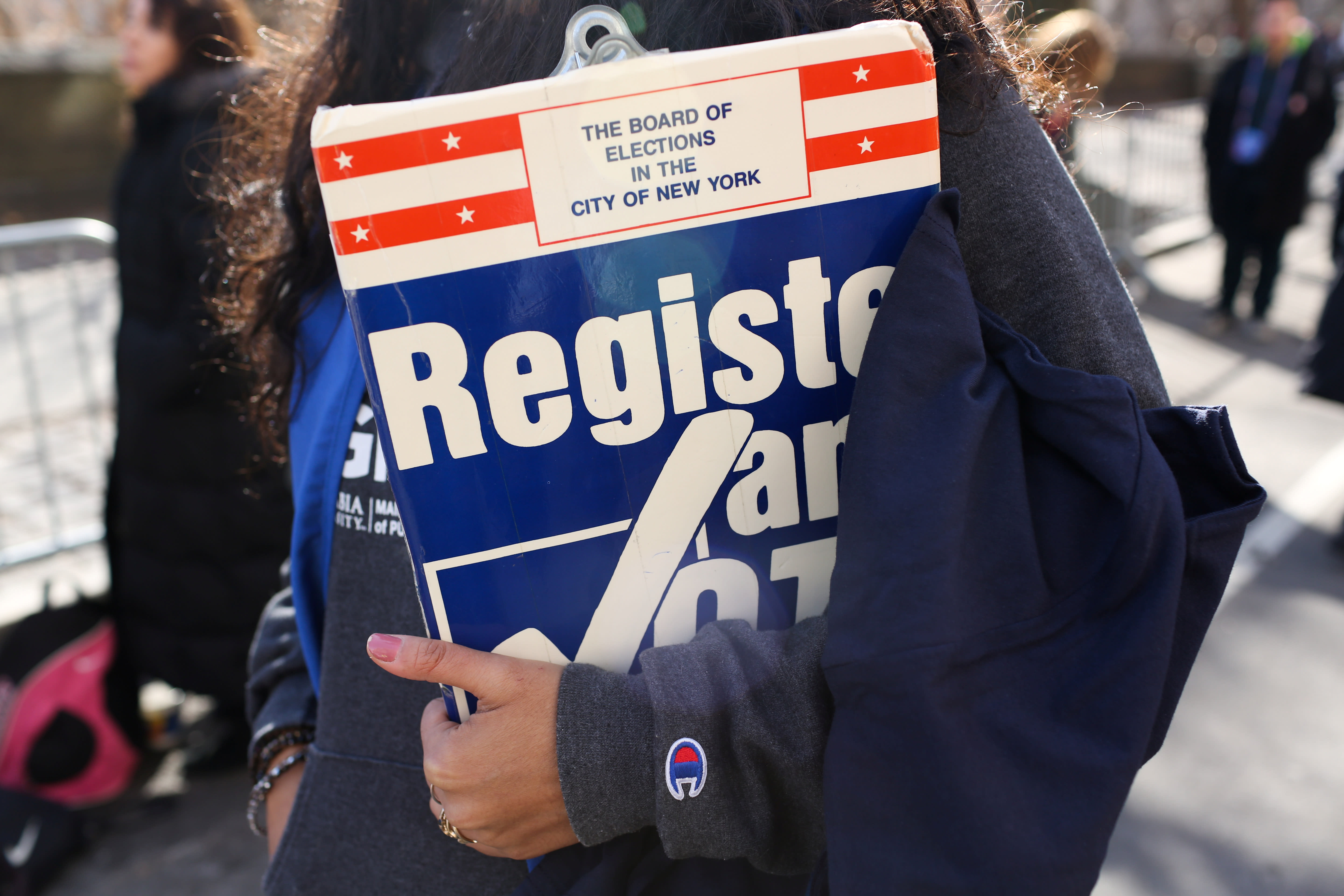 A woman holds a clipboard to register people to vote at Women's March in Manhattan in New York City (REUTERS/Gabriela Bhaskar)