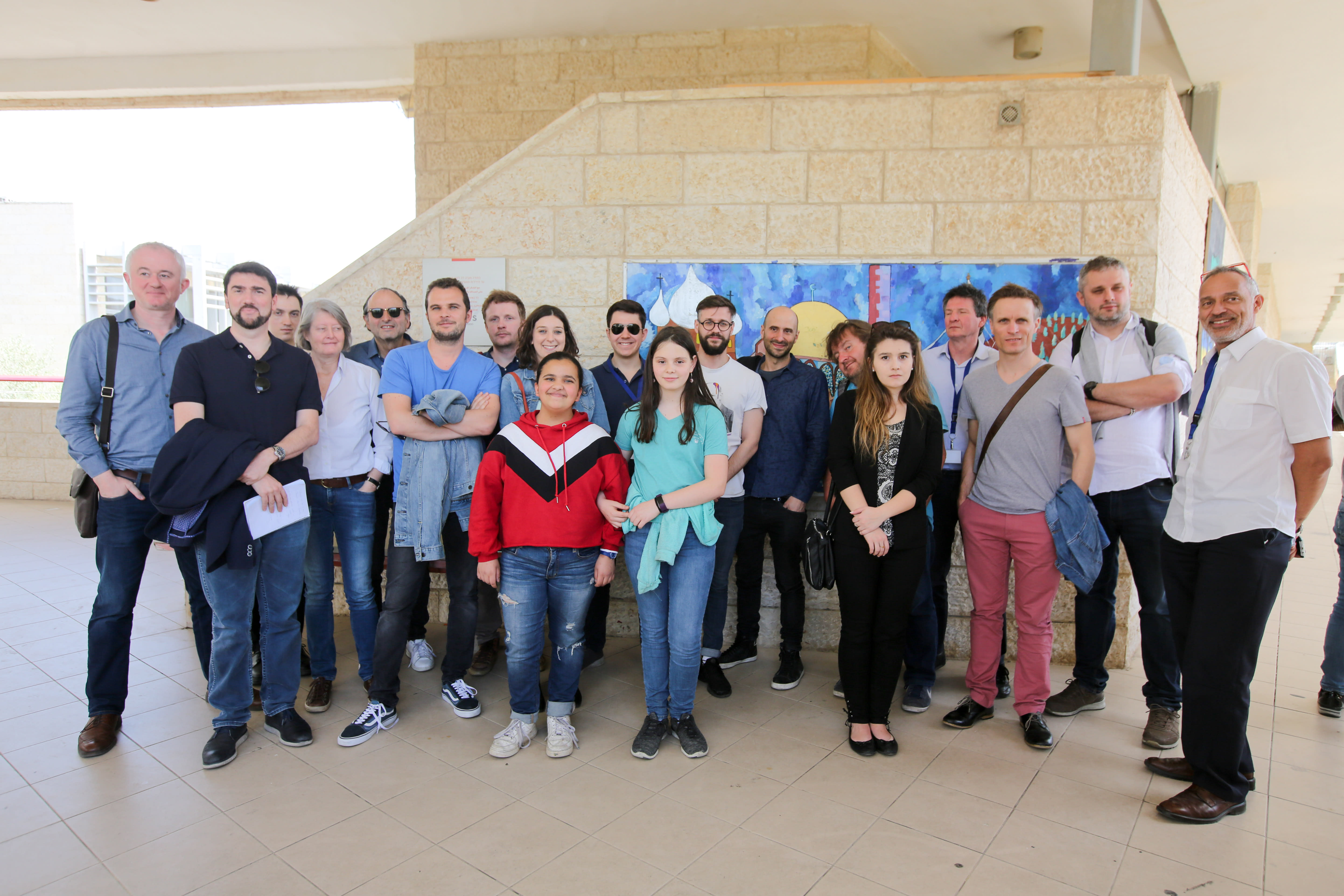 Foreign journalists pose in front of the Jerusalem Hand in Hand School during their visit to Israel
