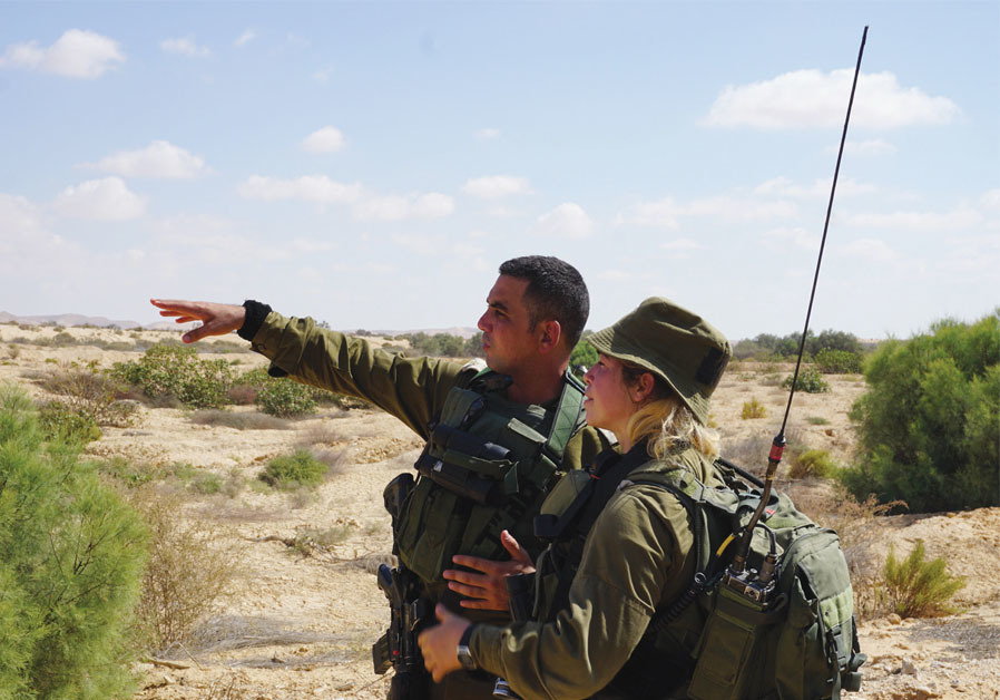 Meeting any threat: Commander Lt.-Col. Shahar Nachmani gestures at the border fence while speaking with one of the soldiers. ( SETH J. FRANTZMAN)