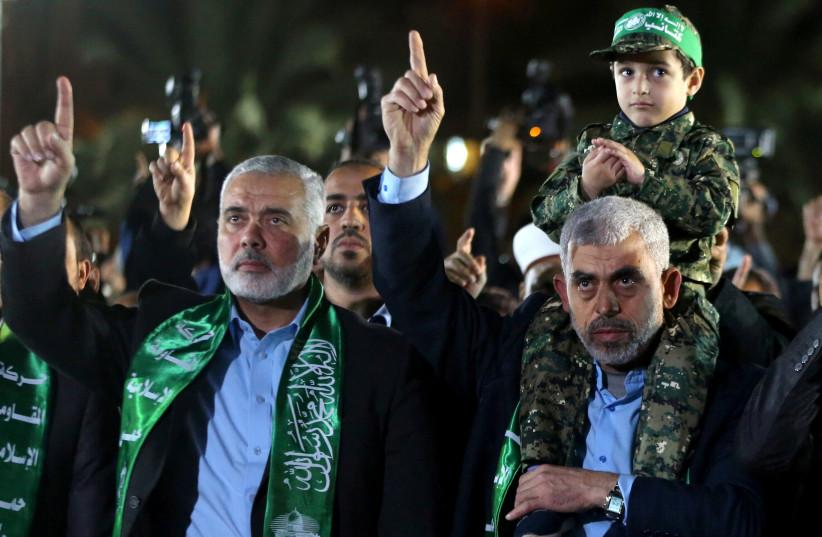 O filho do militante sênior do Hamas, Mazen Fuqaha, senta-se nos ombros do chefe do Hamas Gaza, Yahya Al-Sinwar, como líder do Hamas, Ismail Haniyeh (L), gestos durante um serviço memorial para Fuqaha, na cidade de Gaza, em 27 de março de 2017 (crédito da foto: REUTERS)