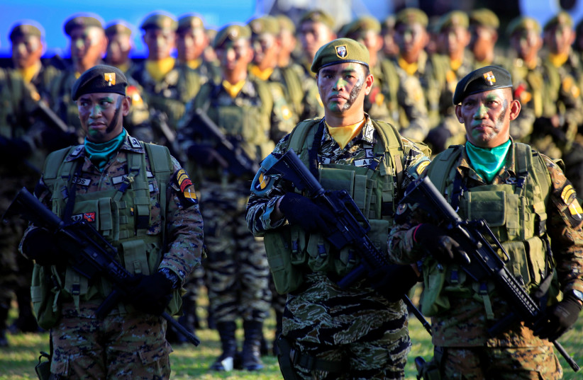 Soldiers holding their weapons stand on attention during the 121st anniversary celebration of the Philippine Army at Taguig city, Metro Manila, Philippines March 20, 2018 (photo credit: ROMEO RANOCO/REUTERS)