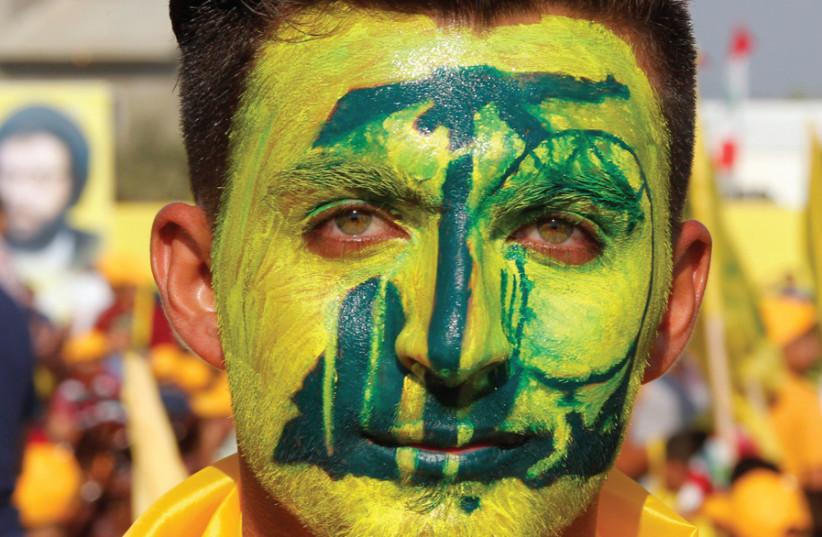Un soutien portant le logo du Hezbollah peint sur son visage pose pour une photo lors du rassemblement marquant le 10e anniversaire de la fin de la guerre de 2006 à Bint Jbeil, dans le sud du Liban, le 13 août 2016. (crédit photo: AZIZ TAHER / REUTERS )
