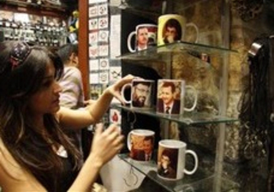 A Syrian woman looks at mugs imprinted with pictur