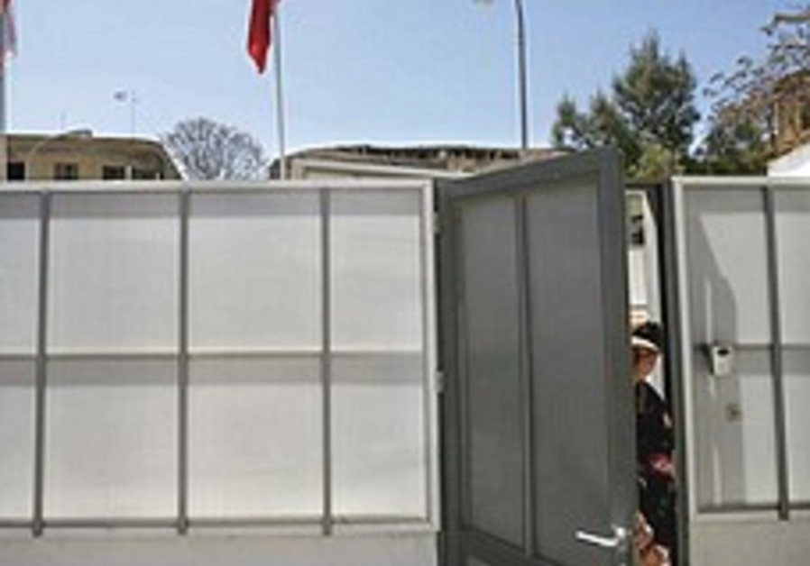 Turkish soldier opens door in temporary wall by UN