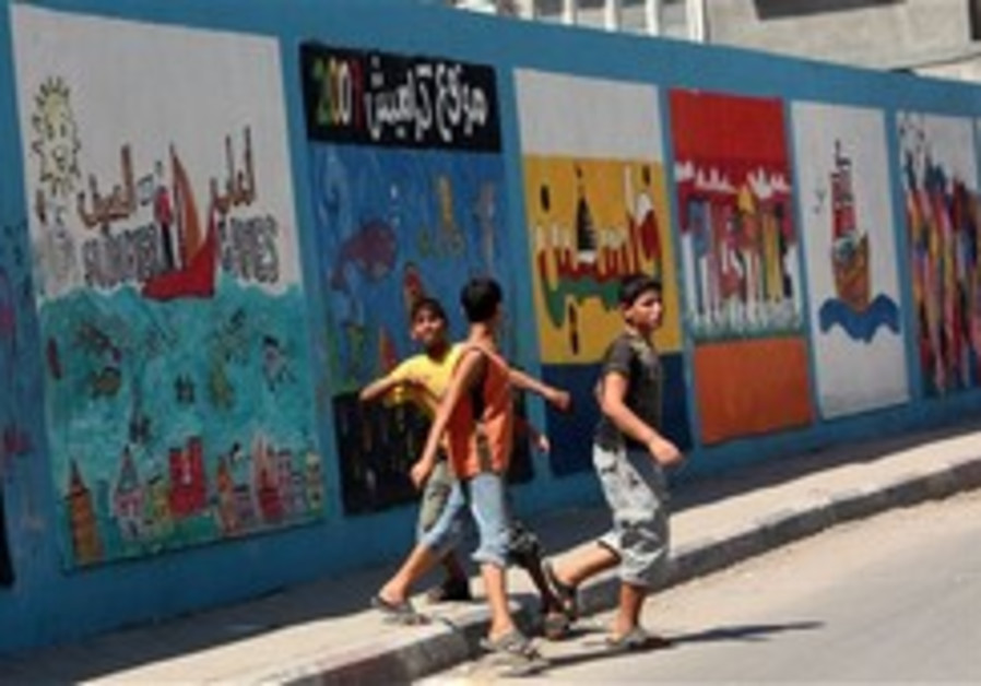 Palestinian youths walk next to a wall of a school