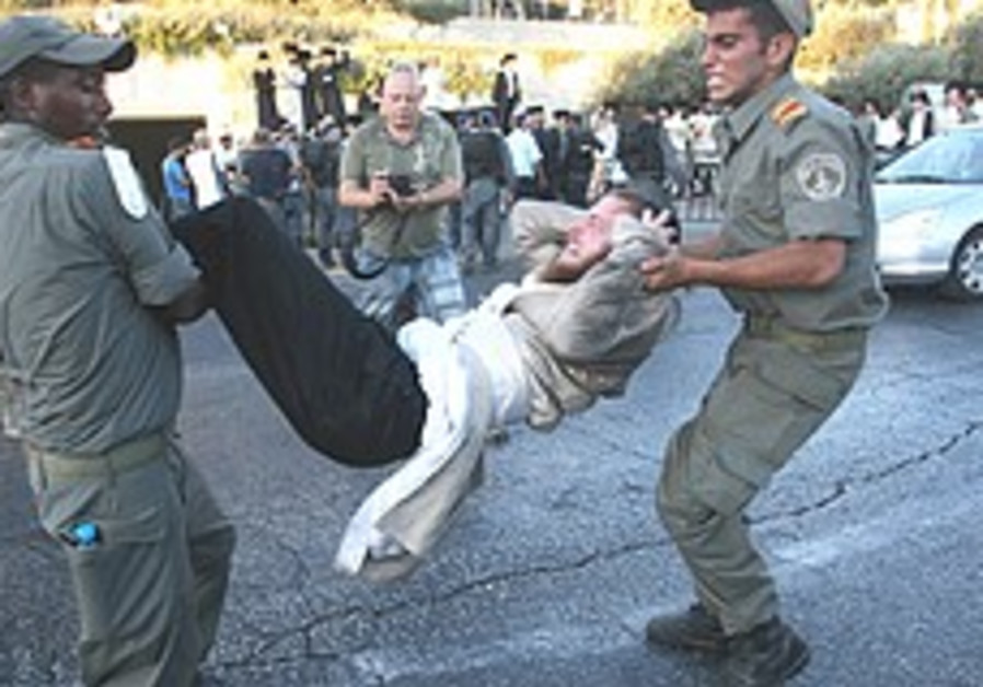 Police remove haredi protesters trying to block tr
