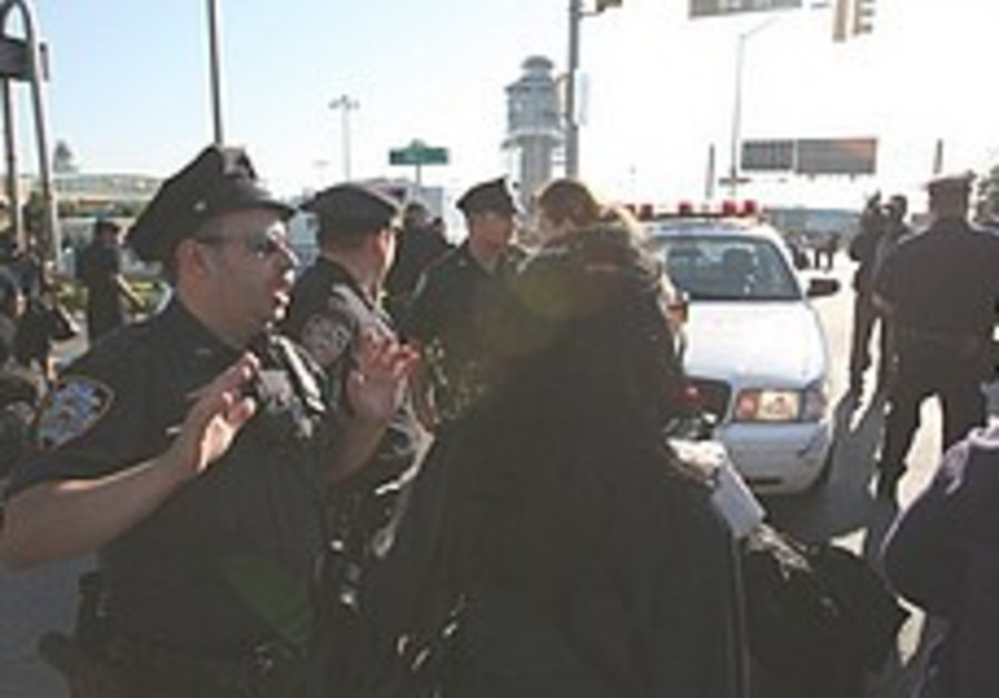 A police officer shouts instructions to a crowd ou