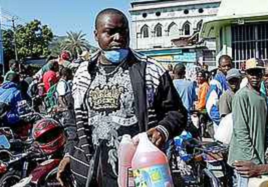 A man holds two bottle of fuel in Haiti