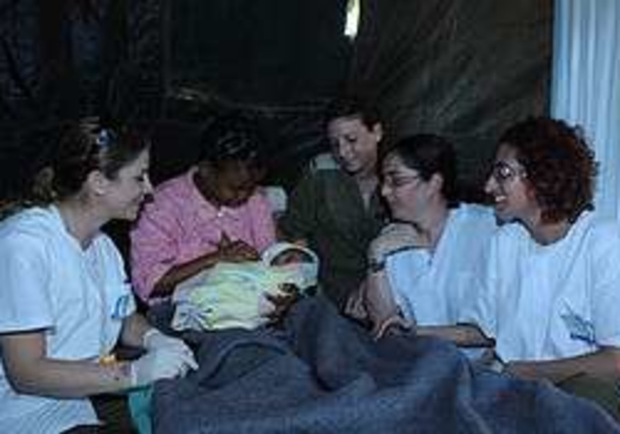 A mother holds her baby in Haiti's IDF field hospi