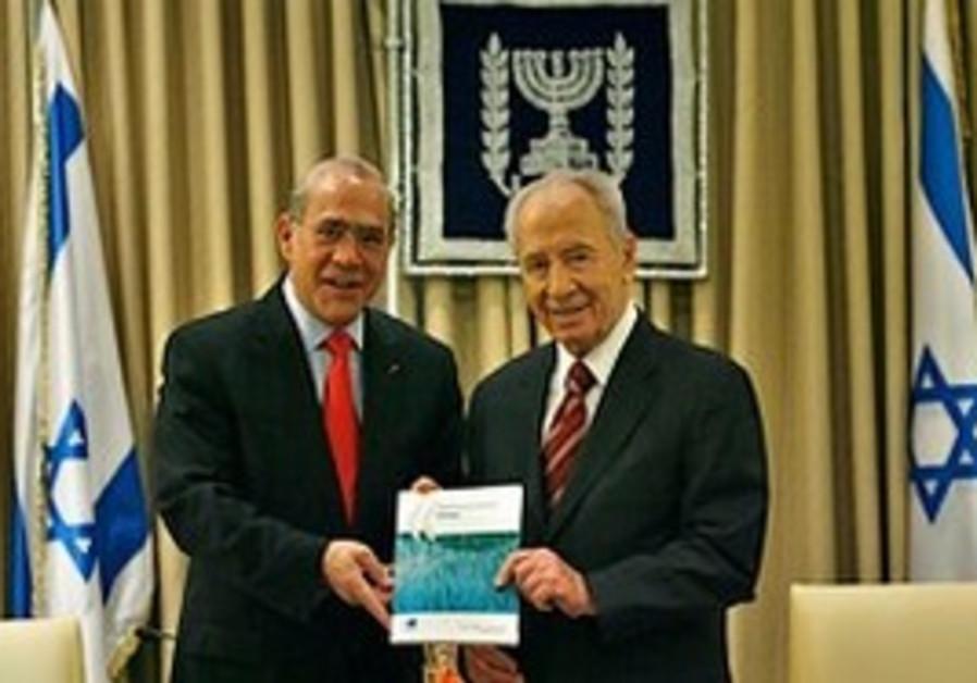 OECD sec.-gen. Gurria hands Peres a recent report,