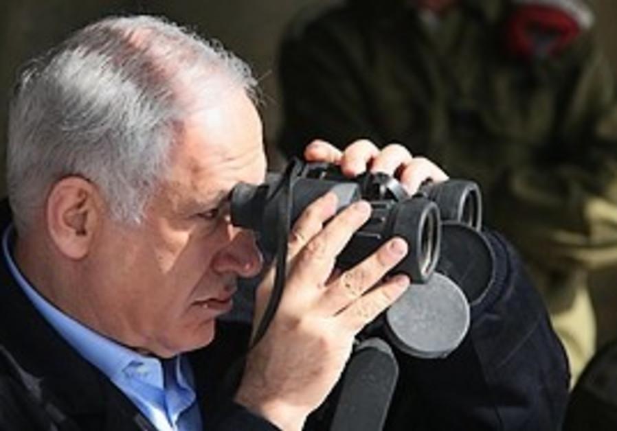 Prime Minister Binyamin Netanyahu looks through bi