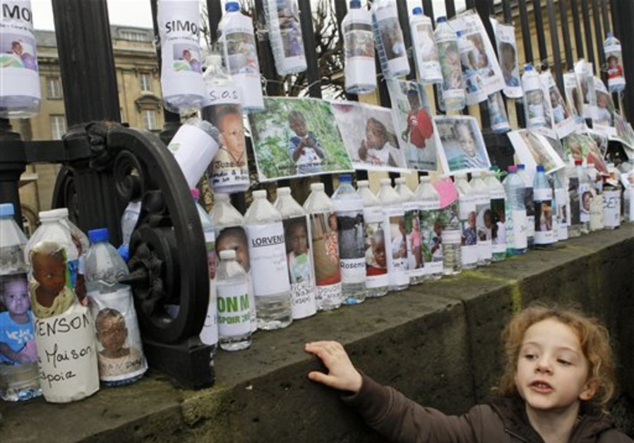 A child looks at water bottles bearing the photos