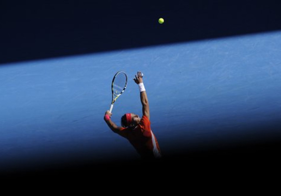 Rafael Nadal of Spain serves to Ivo Karlovic of Cr