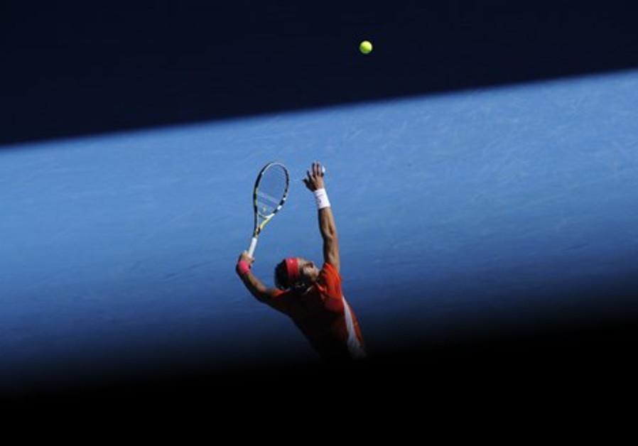 Rafael Nadal of Spain serves to Ivo Karlovic of Cr