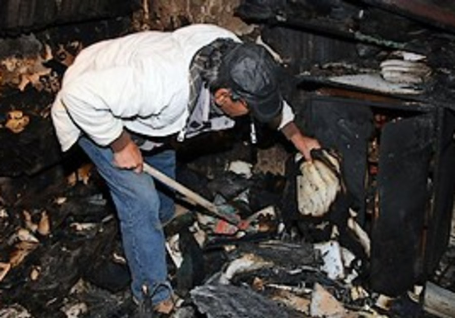 A man looks at the burned Etz Hayyim Synagogue in