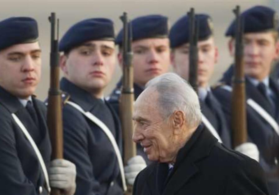 President Shimon Peres passes an honor guard at Te