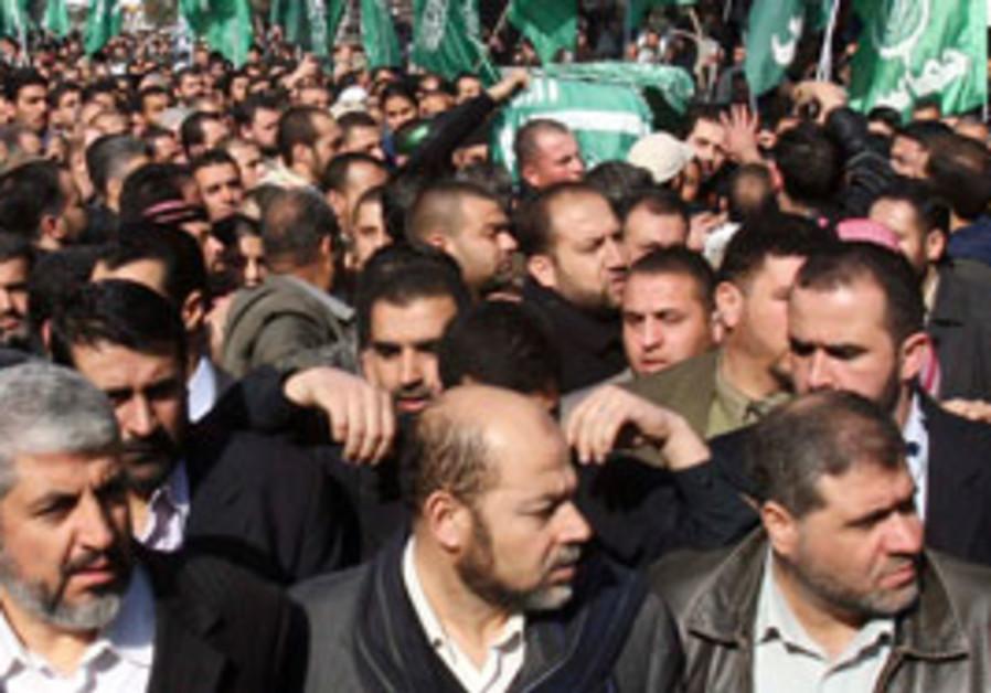 Hamas leader Khaled Mashaal, bottom left, marches