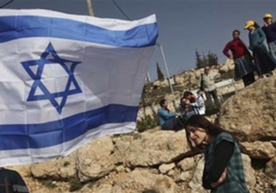 Settler youths watch at a cornerstone ceremony for