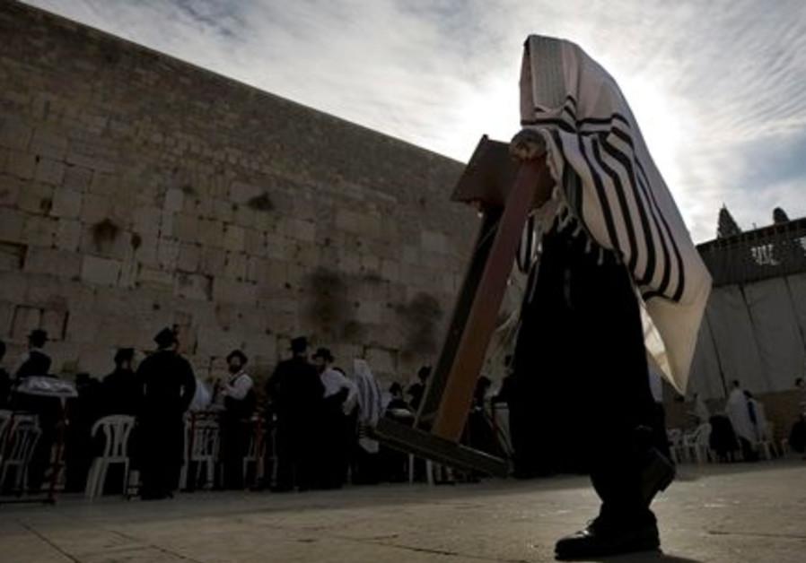 An Ultra Orthodox Jewish man carries a prayer stan