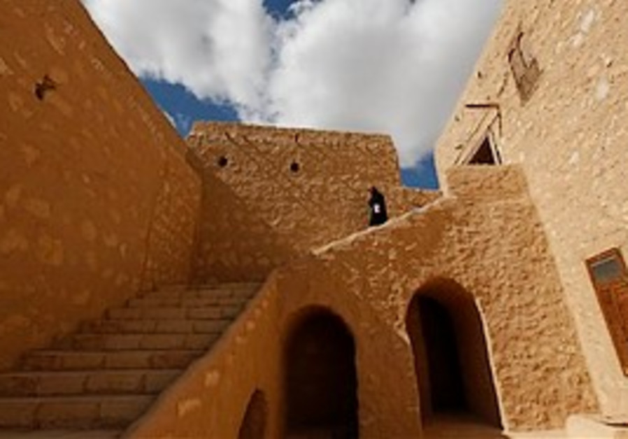 A monk walks down the stairs of the well section,