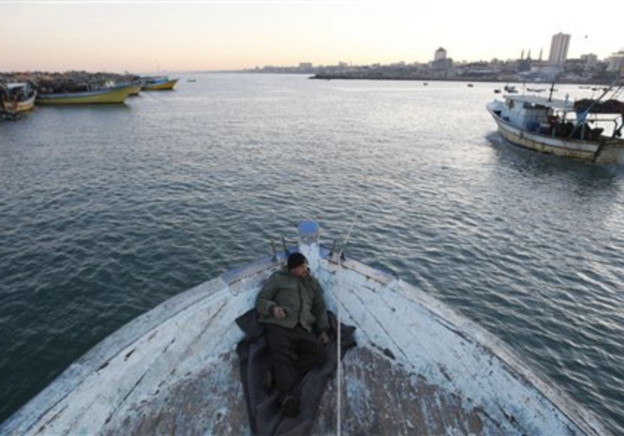 A Palestinian fisherman is seen at sunrise at the