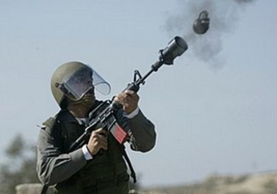 A border police officer fires a tear gas pellet [i
