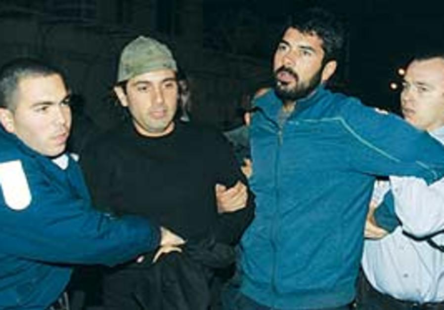 Police detain Tony Copti (center right) and his br