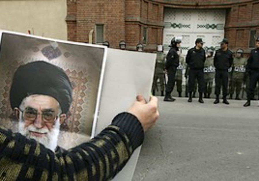 An Iranian protestor holds a picture of the suprem
