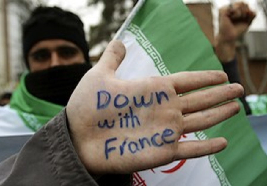 An Iranian protestor shows his hand with an anti-F