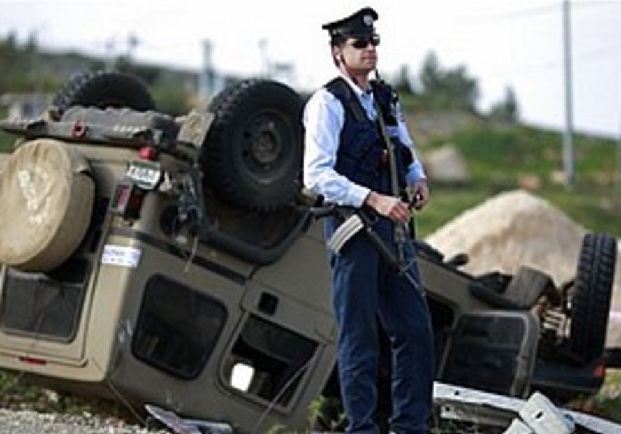 A police officer stands next to a turned-over mili