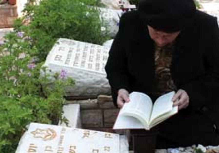 A woman prays at a grave. [illustrative]