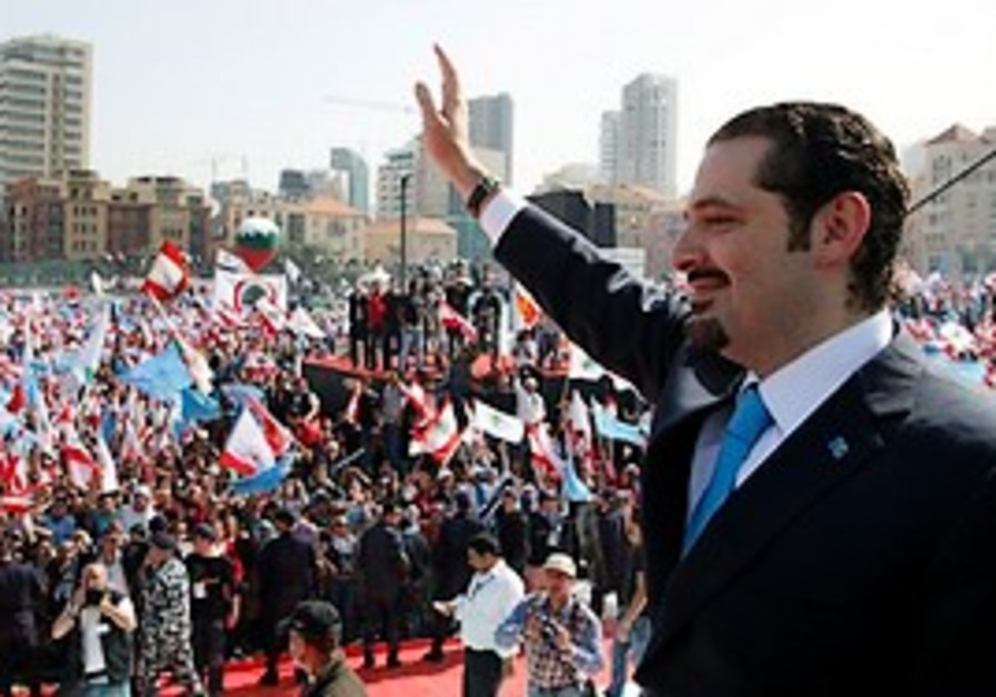Lebanese Prime Minister Saad Hariri, right, waves