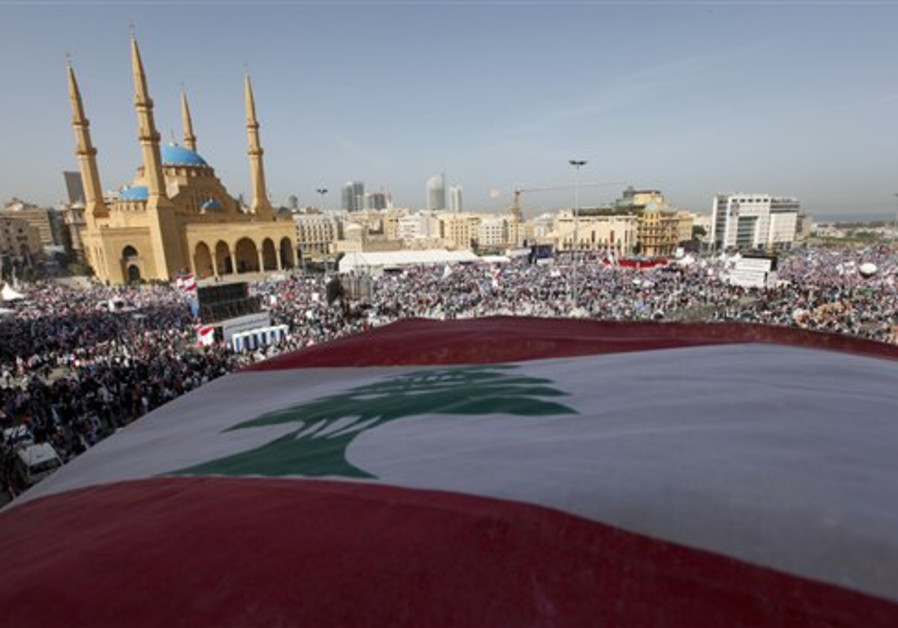 A huge Lebanese flag is seen as thousands of peopl