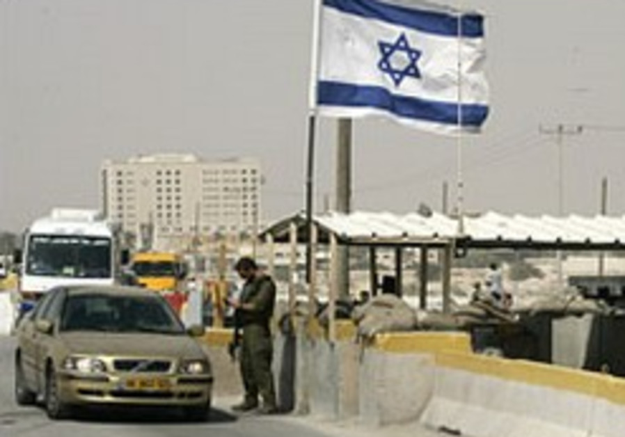 An IDF soldier inspects a Palestinian vehicle at t